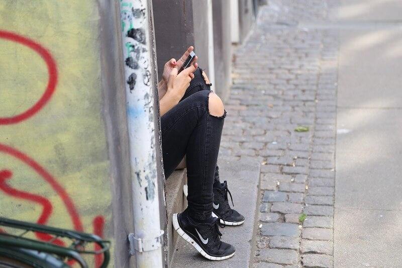 girl hiding o street with mobile phone