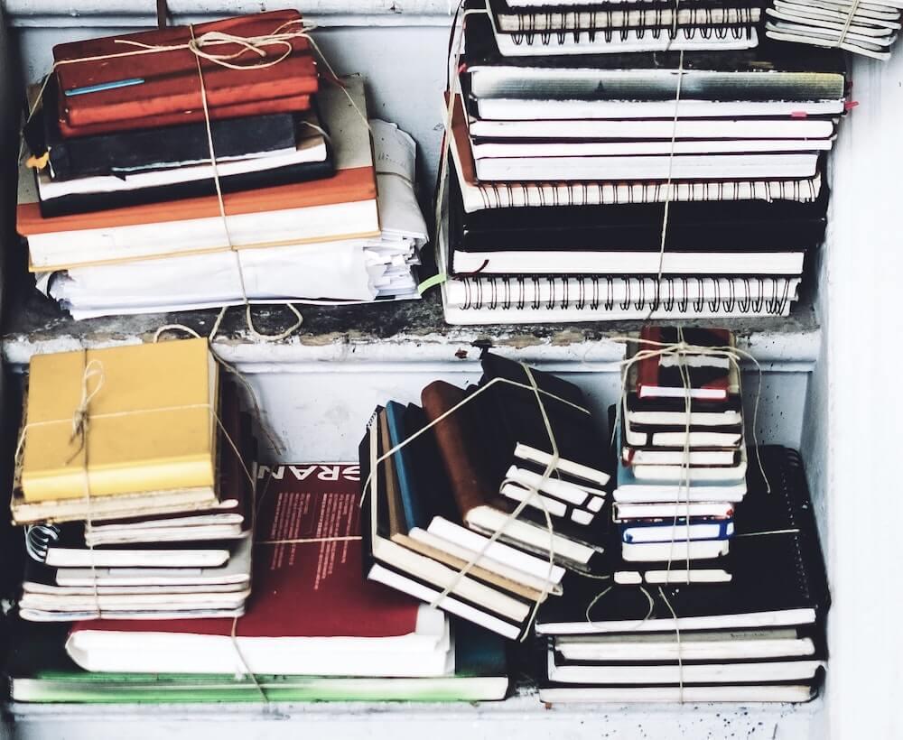 stack-of-notebooks-on-shelves