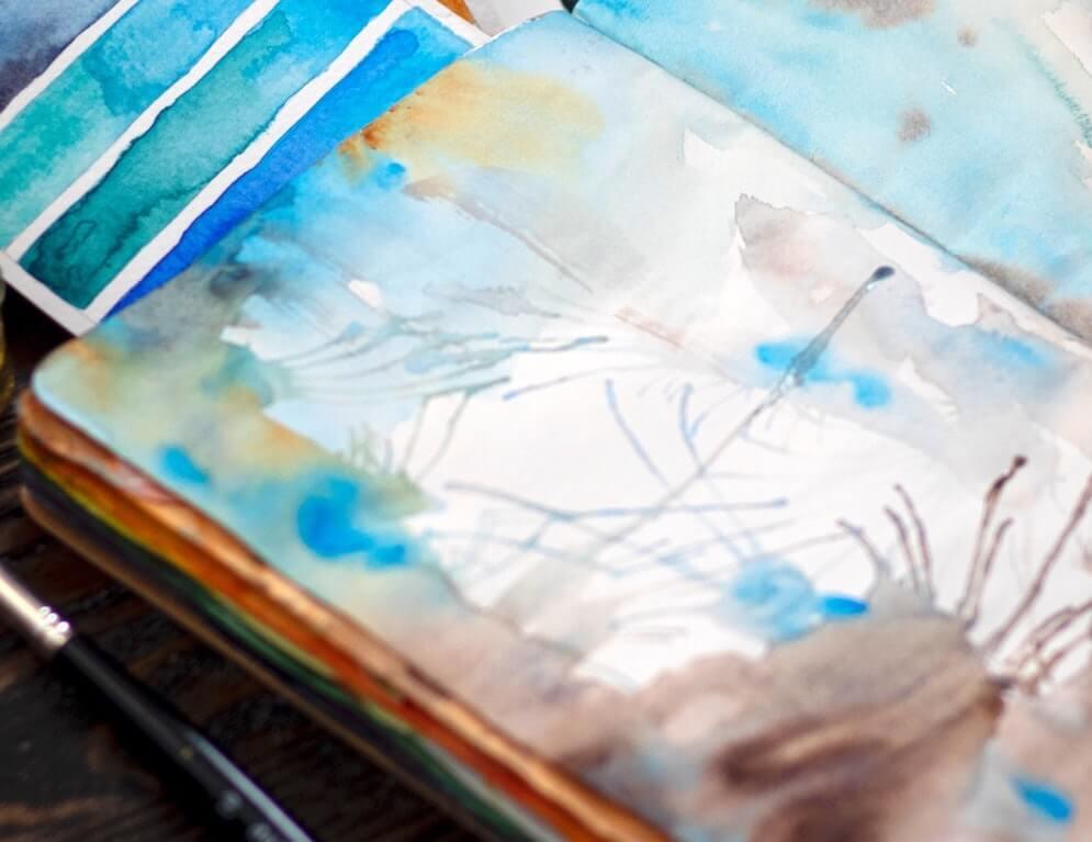 blue paint on open notebook